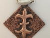 Copper fleur delis pendant created by chase and repousse with a sterling silver bale.