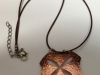 Hand-pierced hammer textured copper pendant with leather cord